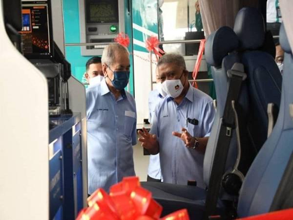 Syed Abdul Aziz (kanan) memberikan penerangan kepada Wan Junaidi (kiri) mengenai perkhidmatan Bank Bergerak yang dilancarkan di Sarawak, pada Khamis.