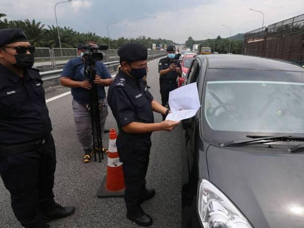 Mohd Nadzri membuat pemeriksaan surat rentas negeri pengguna jalan raya yang melalui Lebuh Raya PLUS di Seremban pada Selasa.