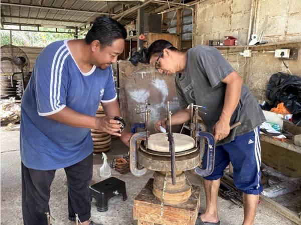 Mokhtar (kiri) menunjukkan proses pemasangan kulit kambing yang menjadi bahan utama dalam pembuatan kompang. - Foto Bernama