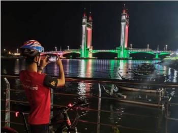 Penunggang basikal yang melalui kawasan itu merakam gambar drawbridge yang diwarnai cahaya bendera Palestin bermula malam ini.