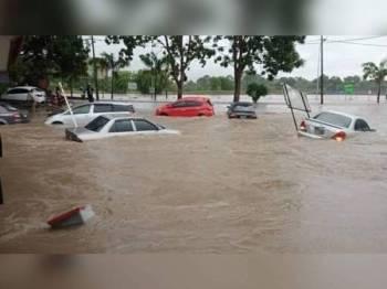 Keadaan Kolam Takungan Banjir Sungai Putat yang diibaratkan seperti pulau dalam kejadian banjir di sini pada Isnin.