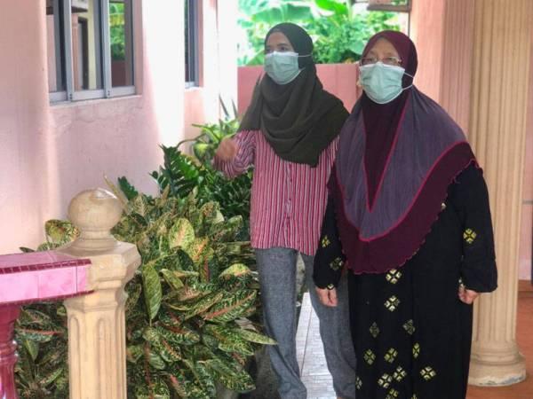 Dua beranak bekas pesakit Covid-19, Rosalwani Che Soh, 40, (kiri) dan ibunya, Zainab Mahmood,76, menunggu giliran dipanggil oleh Jabatan Kesihatan Kelantan bagi mendapatkan vaksin