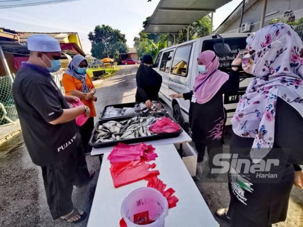 Mohd Zatullah (kiri) melayan penduduk yang mahu membeli ikan.