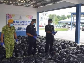 Shamsudin (kanan) menunjukkan rampasan daun ketum bernilai RM100,000 di Ibu Pejabat Polis Daerah Baling pada Ahad.