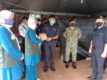 Maziah (dua dari kiri) menyampaikan sumbangan Rumah Ngaji Teluk Muroh kepada petugas barisan hadapan sebagai tanda penghargaan di sekatan jalan raya sekitar daerah Manjung pada Jumaat.