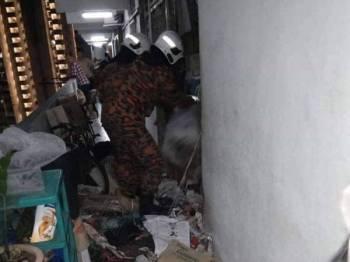 Anggota bomba sedang melakukan kerja-kerja menyelamatkan mangsa terperangkap  di bawah timbunan sampah di dalam rumahnya di Apartmen Bukit Saujana, Jalan Paya Terubong, Georgetown.