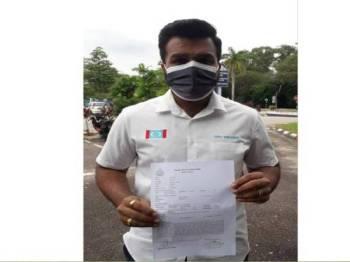 Suria Vengadesh menunjukkan salinan laporan polis yang mendesak polis melakukan siasatan dan tindakan terhadap Takiyuddin di pekarangan IPD Seri Alam, Pasir Gudang pada Sabtu.