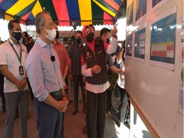 Muhyiddin mendengar taklimat ketika melawat PPV Bukit Gambir pada Selasa.