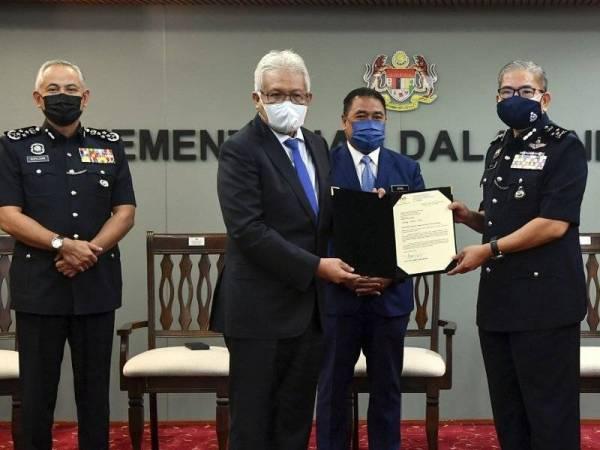Hamzah menyerahkan watikah pelantikan Timbalan Ketua Polis Negara kepada Mazlan di Kementerian Dalam Negeri hari ini. - Foto Bernama