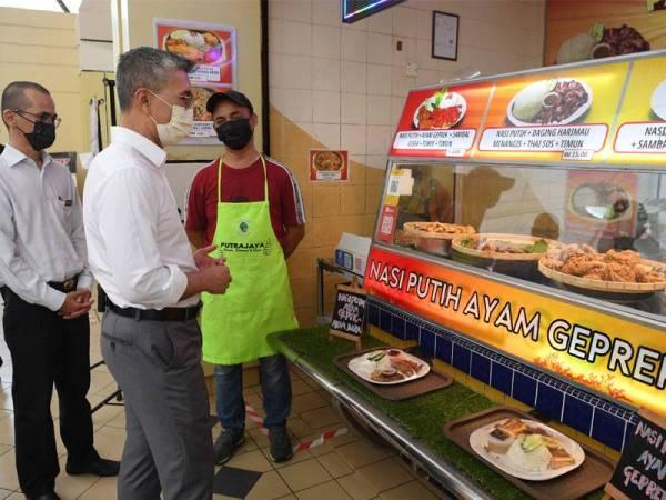 Tengku Zafrul (kanan) beramah mesra dengan seorang peniaga pada program Tinjauan Mesra ke Kiosk D'Harmoni@9 dan Medan selera Presint 9 pada Rabu. - Foto Bernama