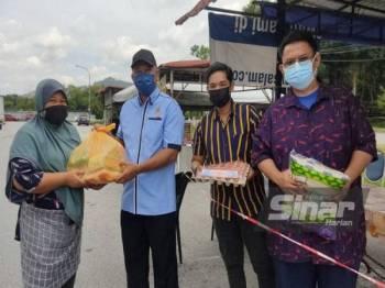Dari kanan; Ahmad Soffian, Pengerusi Qnin Inspired,Mohd Athoillah Amin Mohd Asri dan Zakaria menyerahkan bakul makanan kepada penerima bantuan di Taman Sri Haneco pada Sabtu.