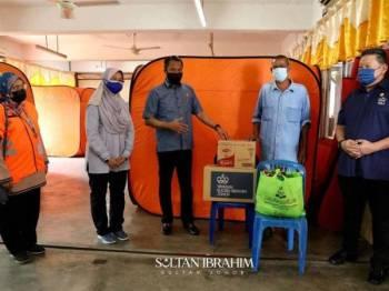 David Wong (kanan) menyampaikan bantuan Sultan Johor kepada mangsa ribut di PPS Sekolah Kebangsaan Seri Setia Jaya, Tanjung Sedili, Kota Tinggi pada Sabtu.