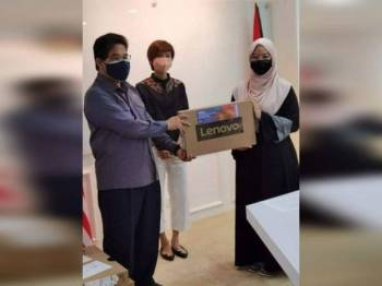 Mohammad Rafie menyampaikan sumbangan komputer riba.