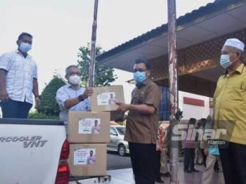Wartawan sambilan Bernama, Adnan Mohamad (dua dari kiri) menerima kotak makanan daripada Che Abdullah.