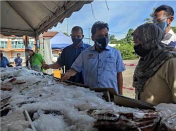 Che Abdullah (tengah) ketika melakukan tinjauan bekalan makanan dan rantaian pemasaran ikan dan mempromosikan ikan segar beku (Q'Fish) LKIM di Pasar Nelayan Seringgit.