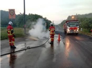 Anggota bomba membantu memadamkan kebakaran sebuah kereta yang terlibat dalam kemalangan akibat tumpahan minyak di KM15, Jalan Felda Mempaga-Chinta Manis, pada pagi Isnin.
