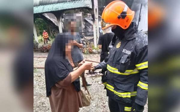 Anggota bomba menyerahkan barang kemas yang ditemui kepada mangsa.