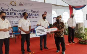Hasni (tiga dari kiri) menyerahkan kunci rumah kepada penduduk bagi projek penempatan semula perumahan di Kampung Pendas Baru Fasa 2 di Iskandar Puteri pada Ahad.