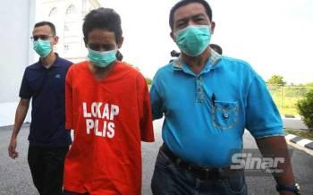 Mohd Zamri (tengah) dikawal ketat polis ketika dibawa ke Mahkamah Sesyen Kota Bharu pada Rabu.