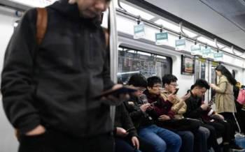 Gambar fail menunjukkan sejumlah penumpang menggunakan telefon bimbit keluaran China di dalam tren di Beijing baru-baru ini. - Foto AFP