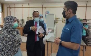 Menteri Kanan Pendidikan, Senator Datuk Dr Mohd Radzi Md Jidin (kanan) meninjau bengkel masakan di Kolej Vokasional Langkawi pada Ahad.