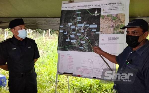 Norddin (kanan) menunjukkan kawasan Hutan Simpan Bukit Lagong yang diceroboh pada Selasa.