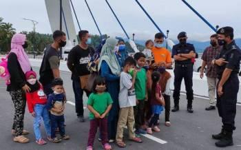 Rohaimi (kanan) bertanya sesuatu kepada pengunjung yang berkunjung ke Tasik Kenyir pada Sabtu.