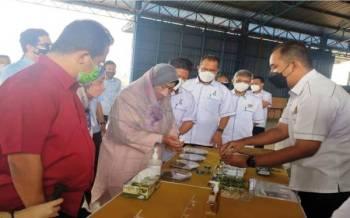 Zuraida (dua, kiri) melihat produk yang dihasilkan daripada kenaf ketika lawatan ke Pusat Pemprosesan Biji Benih Kenaf di Bandar Darulaman, pada Sabtu.
