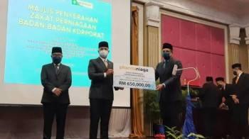 Tengku Amir Nasser (dua, kiri) menerima sumbangan zakat perniagaan daripada Pharmaniaga pada di Hotel GrandMakmur pada Khamis.